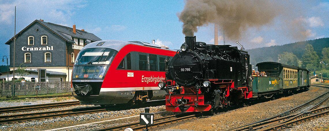 Moderner Triebwagen der Erzgebirgsbahn neben der Dampflok der Fichtelbergbahn