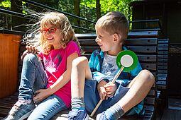 Fröhliche Kinder sitzen auf einer Holzbank im offenen Wagen